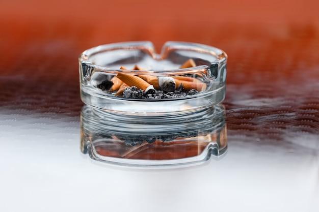 タバコの灰と吸殻の汚れた灰皿 Premium写真