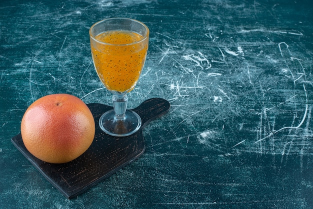 青い背景に加工ジュースとグレープフルーツのガラスのディスプレイ。高品質の写真 無料写真