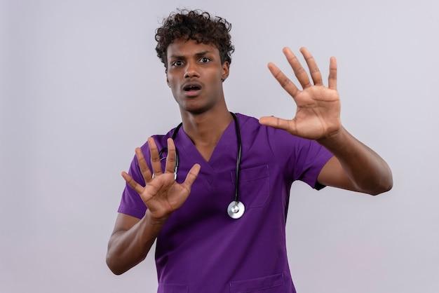 Недовольный молодой симпатичный темнокожий доктор с кудрявыми волосами в фиолетовой форме со стетоскопом пожимает руку без всяких помех. Бесплатные Фотографии