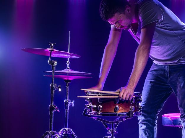 ドラマーは青い壁でドラムを演奏します 無料写真