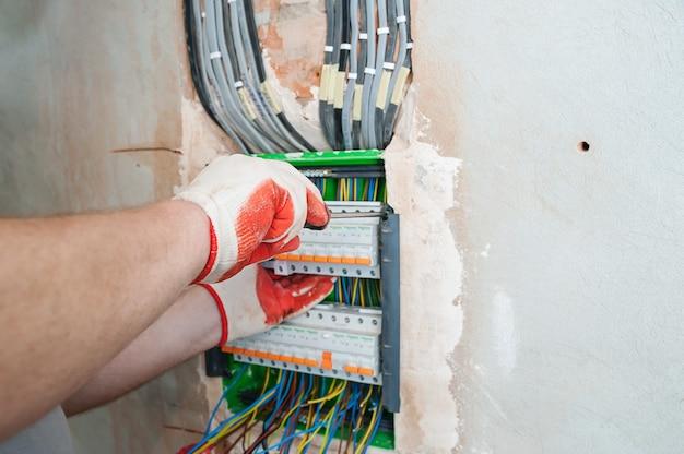 Электрик устанавливает предохранители в распределительную коробку. Premium Фотографии
