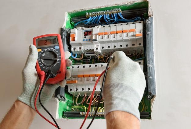 Электрик проверяет мультиметром правильность подключения автоматического выключателя. Premium Фотографии