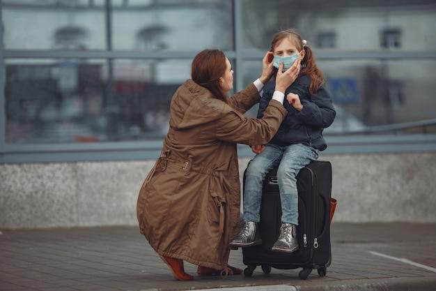 Европейская мать в респираторе с дочерью стоят возле здания. родитель учит своего ребенка, как носить защитную маску, чтобы спасти себя от вируса Бесплатные Фотографии
