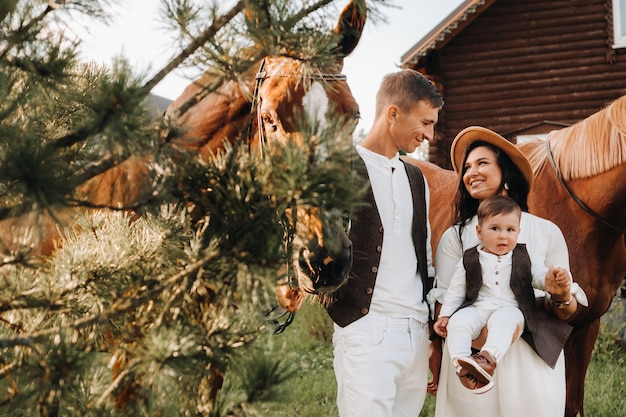 Семья в белых одеждах с сыном стоят возле двух красивых лошадей на природе. стильная пара с ребенком и лошадьми. Premium Фотографии