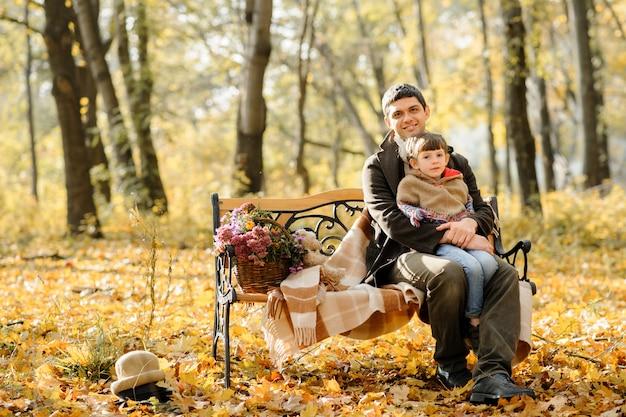 Семья с двумя дочерьми пошла на пикник. осеннее время Premium Фотографии