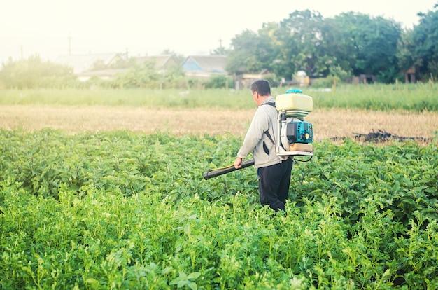 ミスト噴霧器ブロワーを持っている農民は、害虫や真菌感染からジャガイモ農園を処理します Premium写真