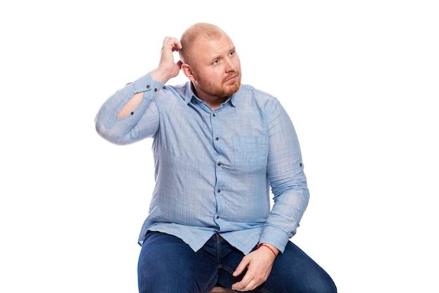 Толстый рыжий мужчина с бородой в синей рубашке и джинсах сидит и чешет голову. изолированные. Premium Фотографии