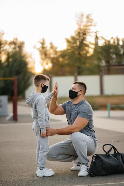 Отец и ребенок стоят на спортивной площадке в масках после тренировки во время заката. Premium Фотографии