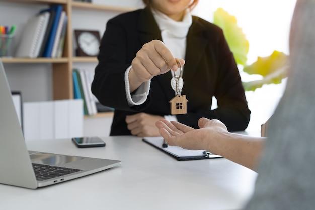 女性の住宅販売代理店がキーホルダーを新しい住宅所有者に手渡した。 Premium写真