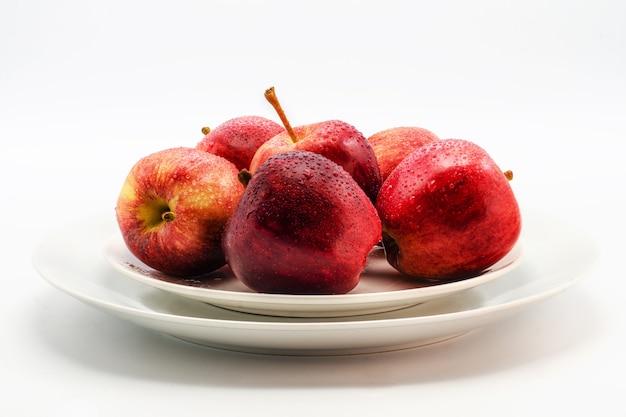 Несколько красных яблок, лежащих на белой тарелке на белом Premium Фотографии