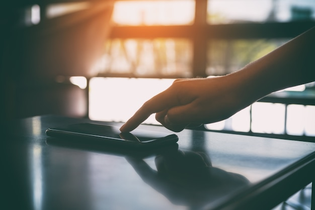 Палец касается и указывает на мобильный телефон на столе Premium Фотографии