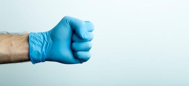 医療用手袋の拳。明るい背景に青い医療用手袋の医師の手。 Premium写真