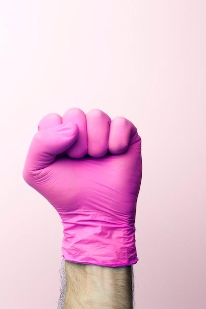 医療用手袋の拳。明るい背景の上のピンクの医療用手袋の医師の手。 Premium写真