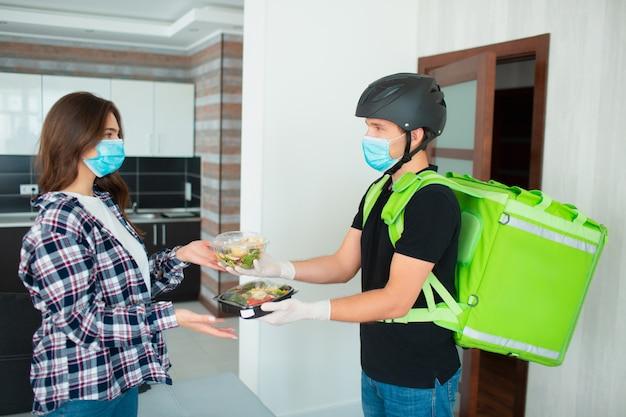 医療用マスクと手袋をした食品配達員が、プラスチックの箱に入った果物と野菜のサラダを若い女性の家に持ってきました。 Premium写真
