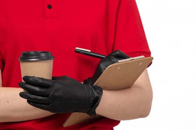 Женский взгляд курьера в красной рубашке, черные перчатки, держа кофе и записывая что-то Бесплатные Фотографии