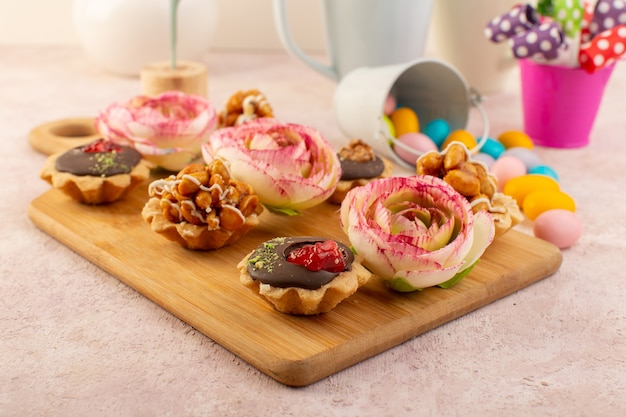 花と色とりどりのキャンディーが並ぶ小さなチョコレートケーキ 無料写真