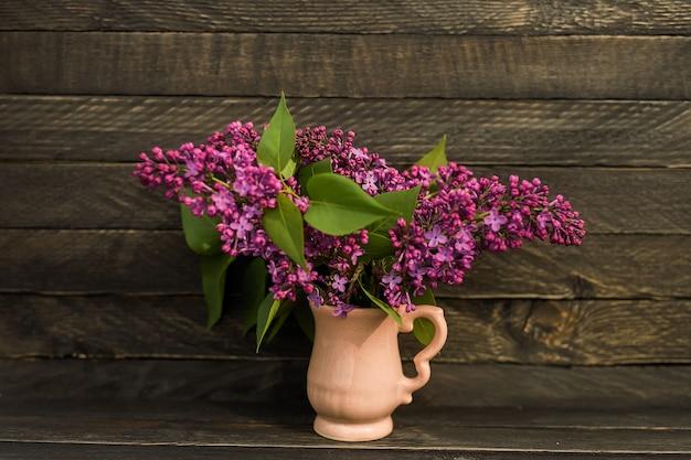 라일락의 향기로운 꽃다발은 소박한 스타일의 나무 벽에 작은 분홍색 주전자에 서 있습니다. 프리미엄 사진