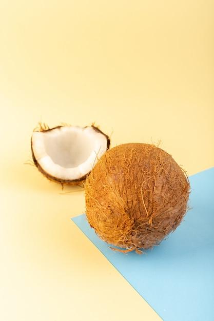 クローズアップビューココナッツ全体とスライスした乳白色の新鮮なまろやかなクリームアイシングブルー色の背景熱帯のエキゾチックなフルーツナッツ 無料写真