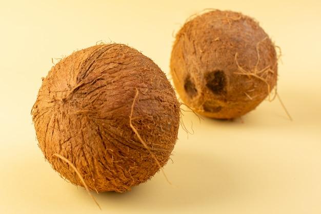 フロントクローズアップビューココナッツ全体の乳白色の新鮮なまろやかなクリーム色の背景に分離された熱帯のエキゾチックなフルーツナッツ 無料写真