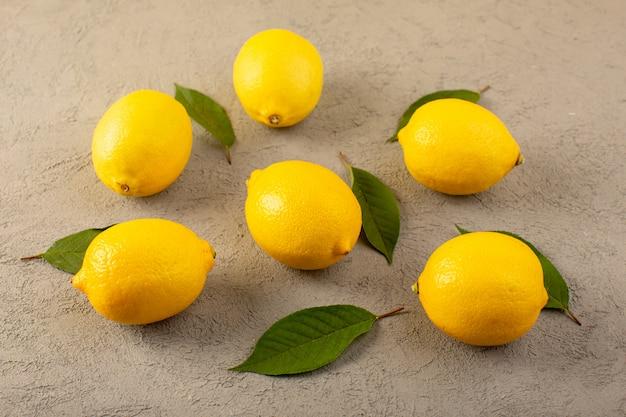 Спереди закрытый вид желтых свежих лимонов спелых сочных спелых с зелеными листьями, выложенными на сером Бесплатные Фотографии