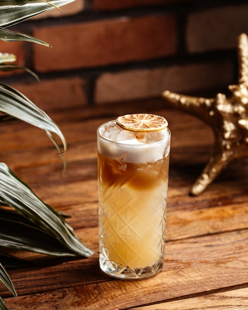 茶色の木製の机の上のガラスの中の正面アルコールカクテル 無料写真