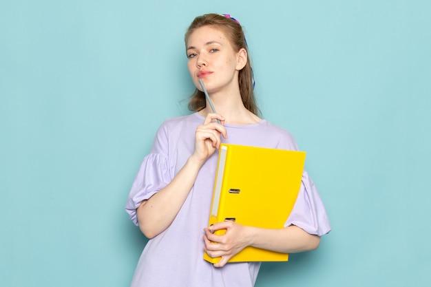 Вид спереди привлекательная женщина в синем платье-рубашке с желтыми файлами на синем Бесплатные Фотографии
