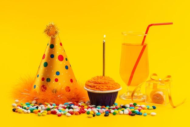 カラフルなキャンディーとバースデーキャップと黄色の色の甘いビスケットのキャンドルと正面の誕生日ケーキ 無料写真