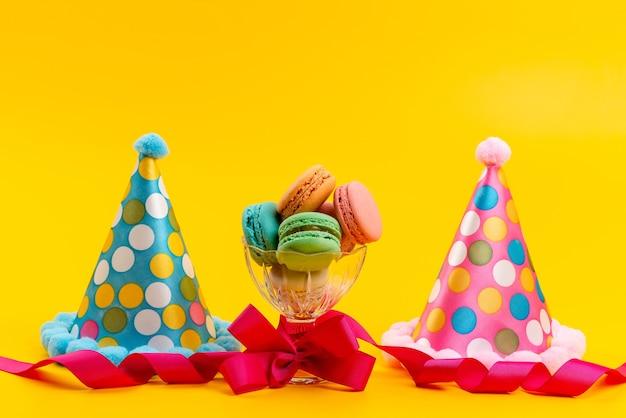 黄色、砂糖の誕生日のお祝いに分離されたフランスのマカロンと一緒に正面のbithdayキャップ 無料写真