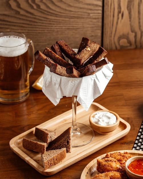 茶色の木製の机の上にソースとチキンの正面図の黒パン 無料写真