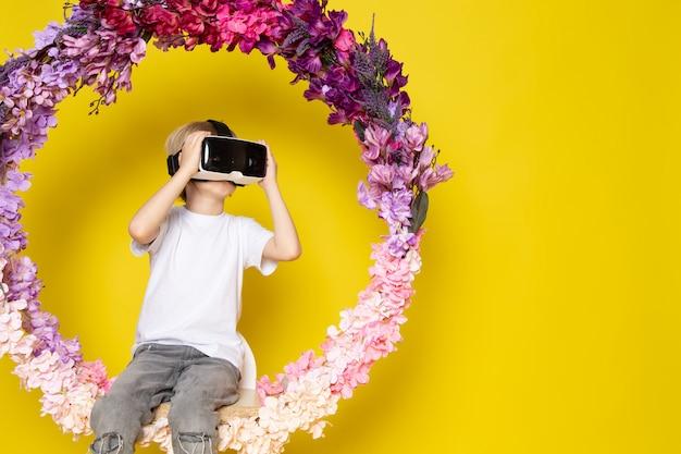 Вид спереди блондин мальчик vr вокруг цветка сделал стенд в белой футболке на желтом полу Бесплатные Фотографии