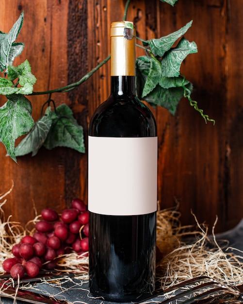 背景アルコールワイナリーの果実と緑の葉と一緒にゴールデンキャップとワイン赤ワインの正面図ボトル 無料写真