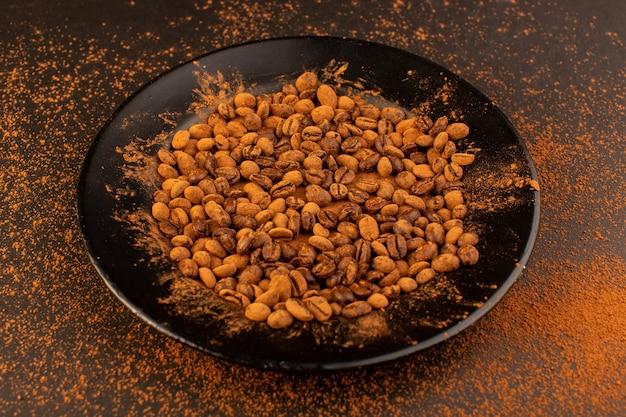 ブラックプレート内の正面の茶色のコーヒー種子 無料写真