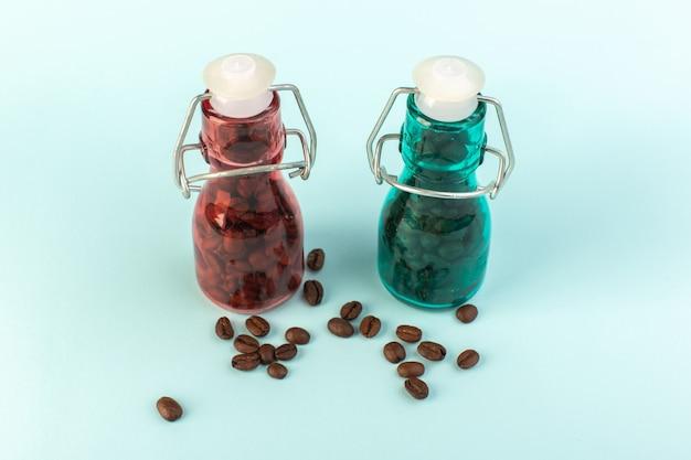 青い表面の着色されたガラスの瓶の中の正面の茶色のコーヒー種子 無料写真