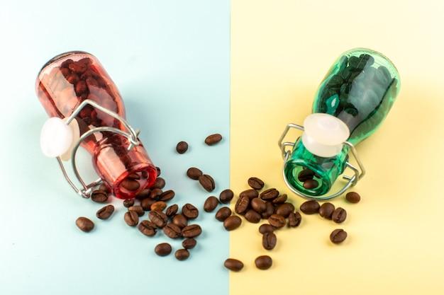 Коричневые семена кофе, вид спереди, внутри цветных стеклянных банок на сине-желтой поверхности Бесплатные Фотографии