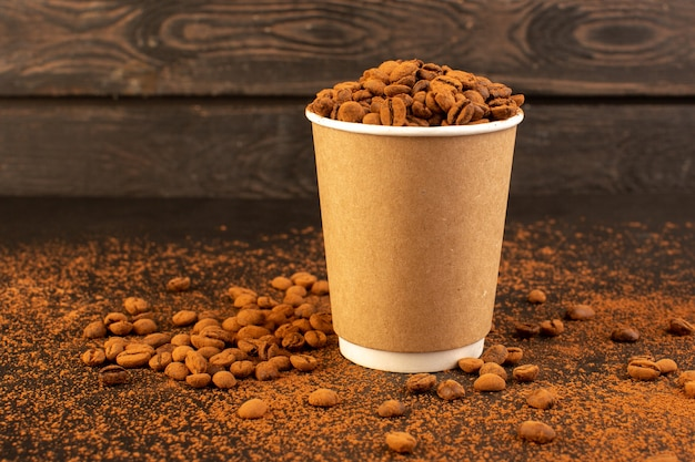 茶色の表面のプラスチックカップ内の正面図の茶色のコーヒーの種とコーヒーの種の暗い粒の顆粒 無料写真