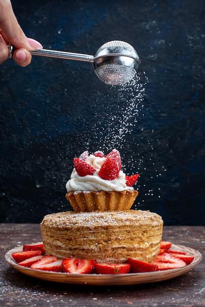 Кусочек торта со сливками и свежей красной клубникой внутри тарелки с сахарной пудрой на темном фоне Бесплатные Фотографии