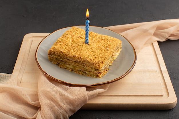 正面のケーキスライスおいしいと木製の机の上のプレートの内側で焼いた、暗いケーキビスケット砂糖甘い 無料写真