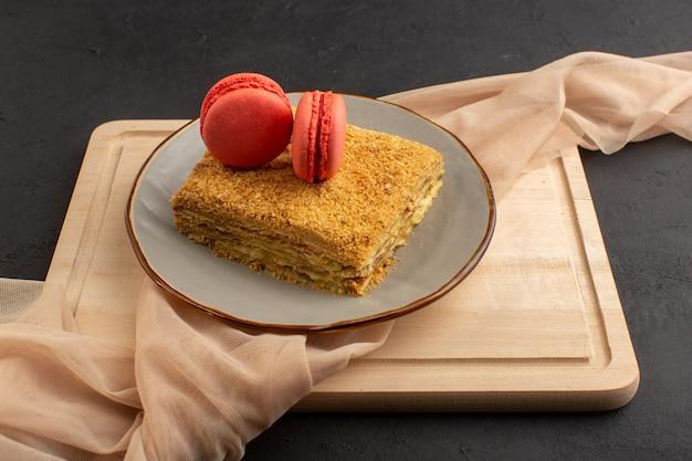 正面のケーキスライスおいしいと木製の机の上のマカロンと暗いケーキビスケット砂糖甘いプレート内焼き 無料写真