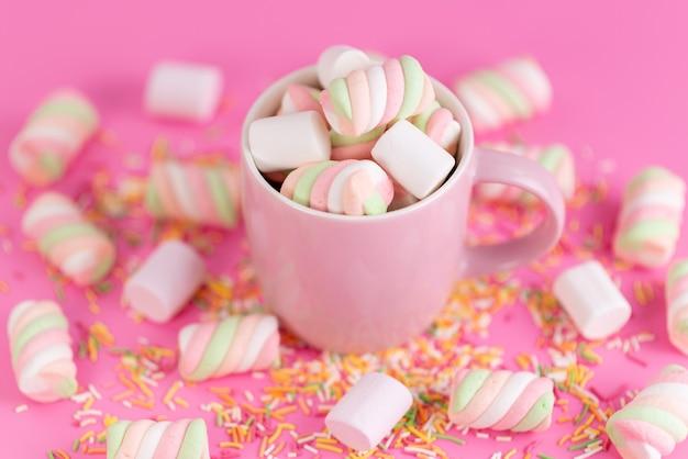 ピンク、カップ、すべてピンク色のレインボーシュガーコンフィチュール内のマシュマロを噛む正面図 無料写真
