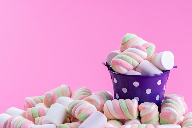 Вид спереди жевательного зефира в фиолетовой чашке и все на розовом, цветном радужном сахарном конфитюре Бесплатные Фотографии