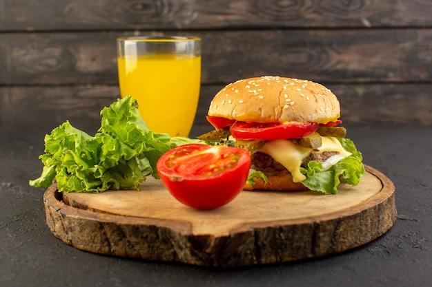 木製の机の上のジュースとサンドイッチとファーストフードのお食事のサンドイッチとチーズとグリーンサラダの正面図チキンバーガー 無料写真