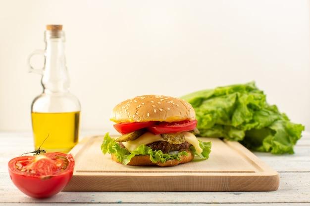 木製の机の上にオリーブオイルとサンドイッチとファーストフードの食事をサンドイッチし、チーズとグリーンサラダと正面から見たチキンバーガー 無料写真