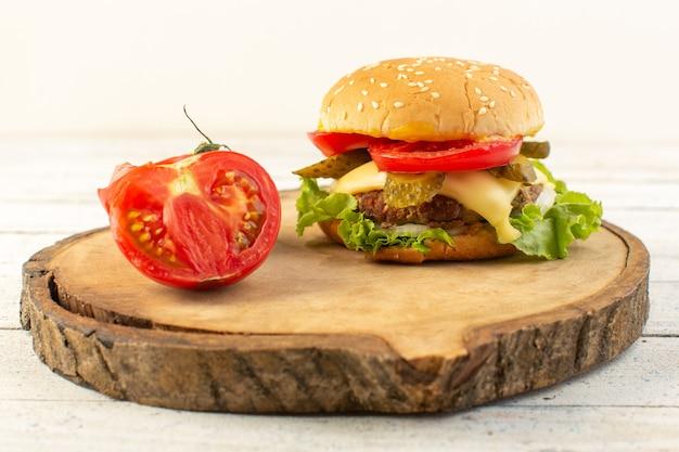 木製の机の上のチーズとグリーンサラダとサンドイッチファーストフードの食事食品の正面図チキンバーガー 無料写真