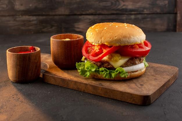 木製の机の上にチーズとグリーンサラダとサンドイッチファーストフードの食事と正面図チキンバーガー 無料写真