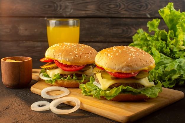 木製の机の上のチーズジュースとグリーンサラダとサンドイッチファーストフードの食事と正面図チキンバーガー 無料写真