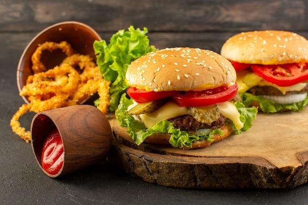 Куриные гамбургеры с сыром и зеленым салатом на деревянном столе и бутерброд фаст-фуд, вид спереди Бесплатные Фотографии