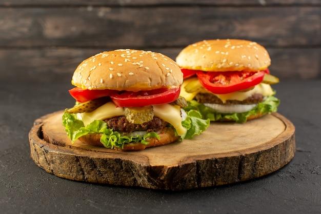 木製の机の上のチーズとグリーンサラダとサンドイッチファーストフードの食事食品の正面図チキンハンバーガー 無料写真