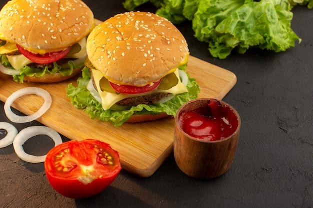 木製の机の上にチーズとグリーンサラダとサンドイッチファーストフードの食事と正面図チキンハンバーガー 無料写真