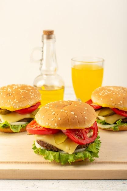 木製の机の上のチーズグリーンサラダジュースとオリーブオイルとサンドイッチファーストフードの食事食品の正面図チキンハンバーガー 無料写真
