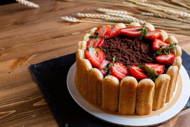 Шоколадный торт спереди, украшенный нарезанным красным клубничным бисквитом круглым вкусным внутри белой тарелке на коричневом столе сладкое печенье кондитерские изделия Бесплатные Фотографии